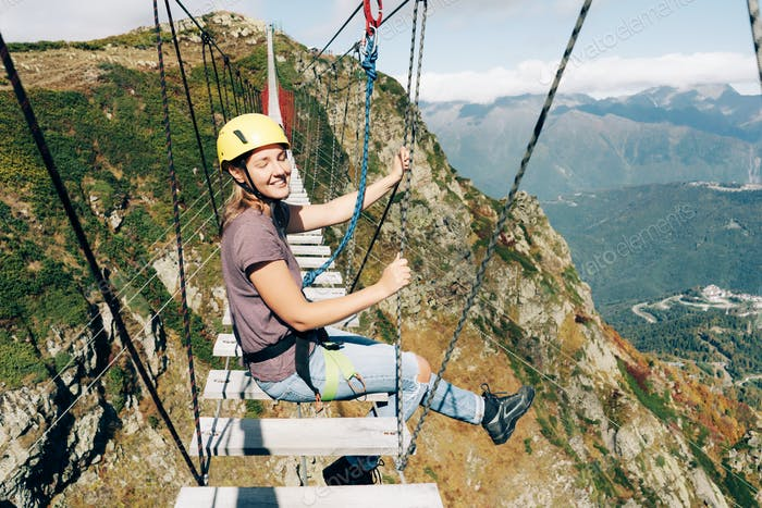 woman in equipment and helmet sits on a suspension bridge high in the mountains