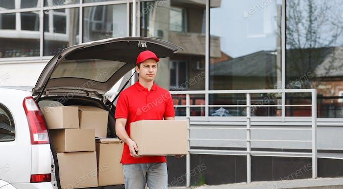 Transport der Box. Kurier mit Paket in den Händen geht zum Kunden nach Hause
