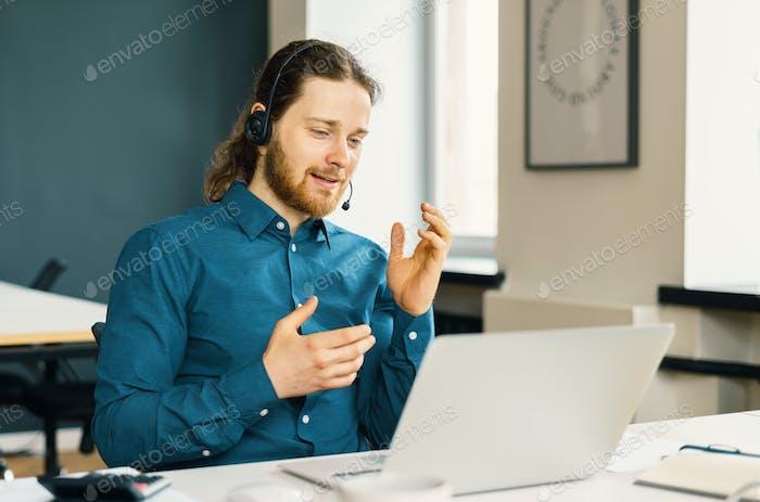 Junger Mann professioneller Callcenter-Betreiber im Headset im Gespräch mit dem Kunden