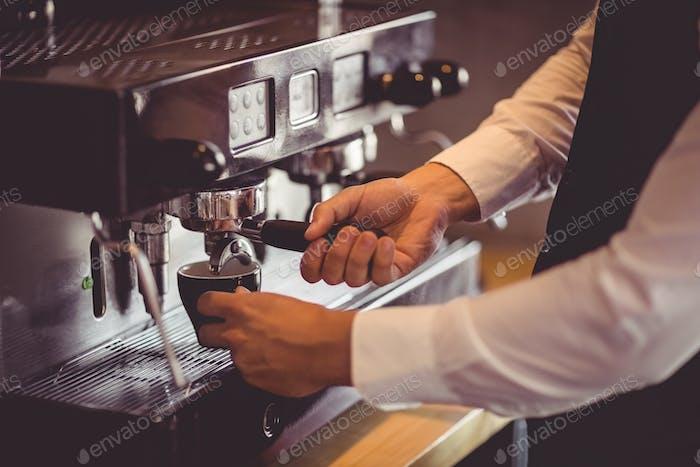 Waiter using coffee machine