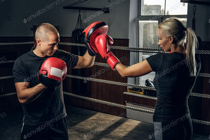 Blonde girl has a training with experienced boxer