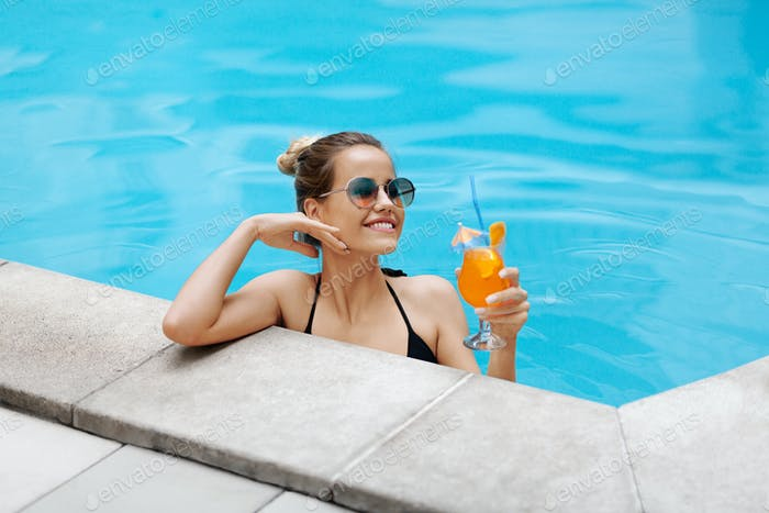 Happy young girl enjoying her refreshing summer cocktail in swimming pool