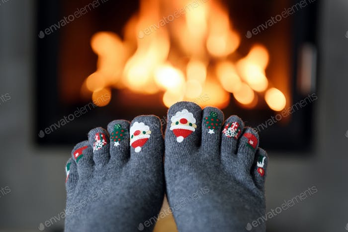 Burning fireplace and girl feet
