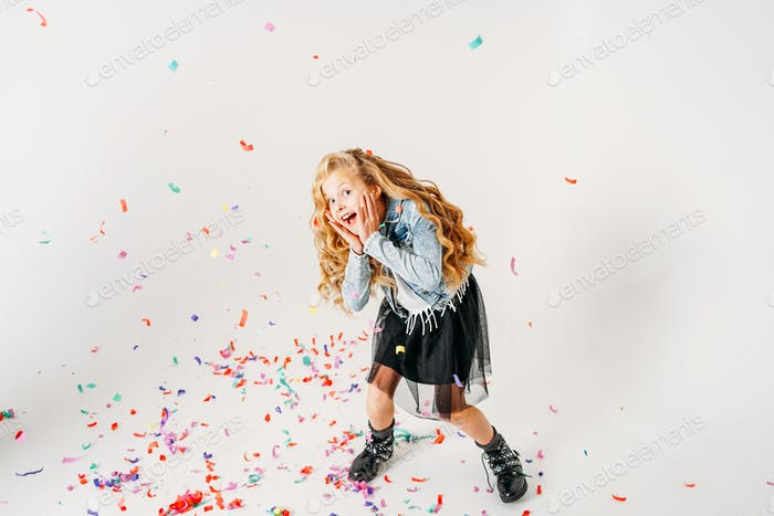 Curly hair girl in denim jacket and black tutu skirt on white background
