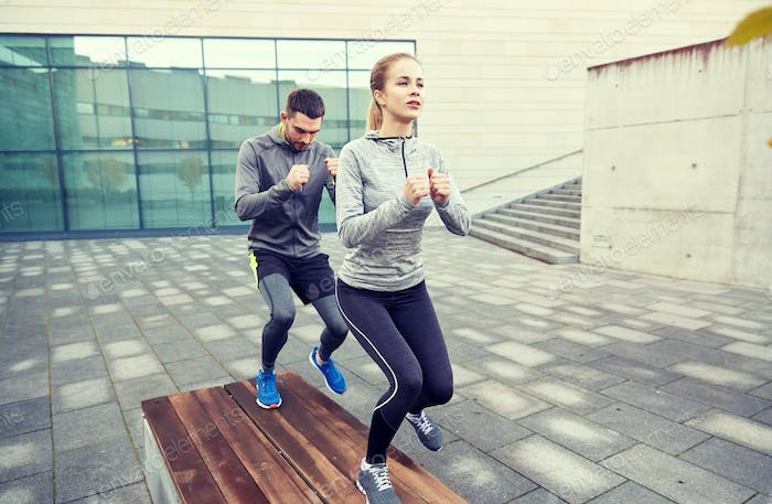 couple making step exercise on city street bench