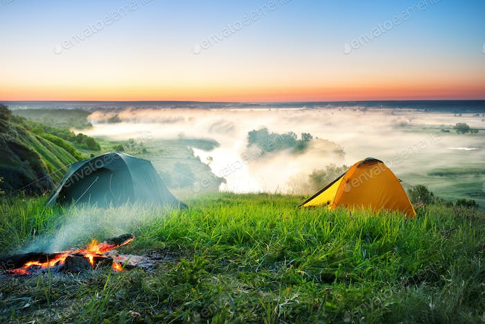 Tent camping on hill over misty river