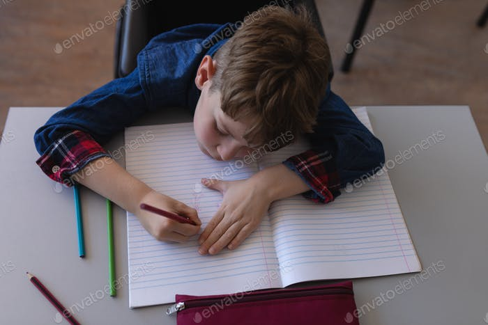 Schoolboy writing on notebook in classroom
