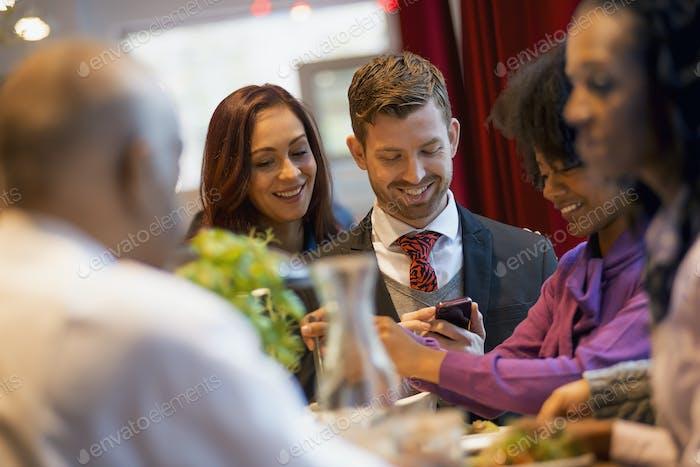 Las personas se mantienen en contacto, usan teléfonos móviles y hablan entre sí en una cafetería