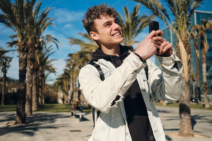 Attractive guy happily taking photo on smartphone during walk along streets with palm trees