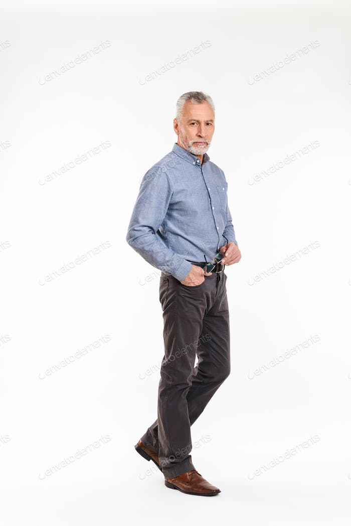 Full-length shot of old man looking camera seriously isolated