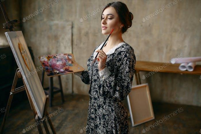 Female painter poses in art studio