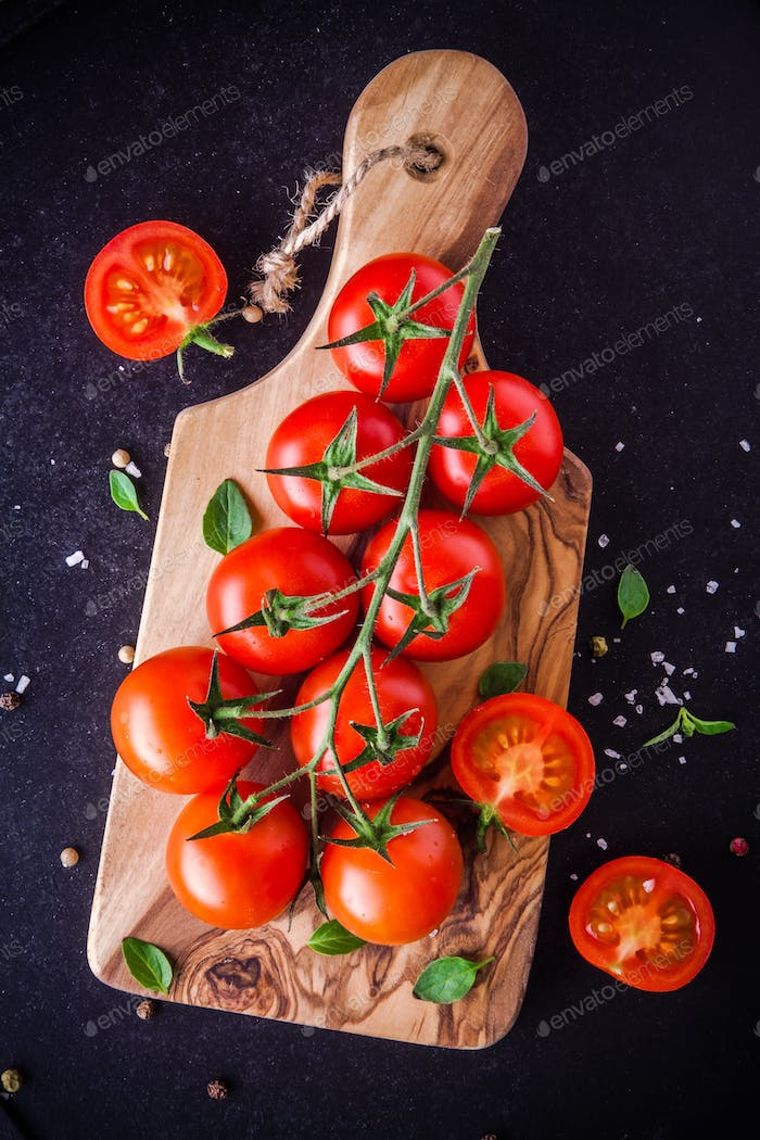 a bunch of fresh organic cherry tomatoes with sea salt and basil in olive cutting board