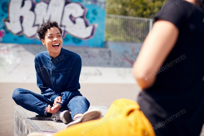 Portrait Of Two Female Friends Meeting In Urban Skate Park