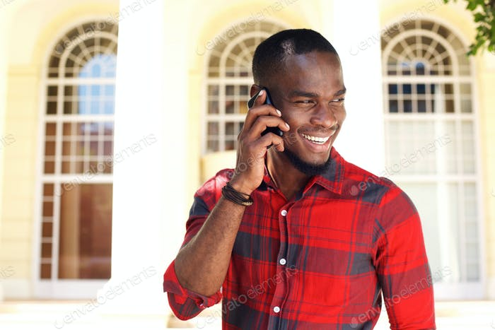 Happy young black guy talking on cell phone