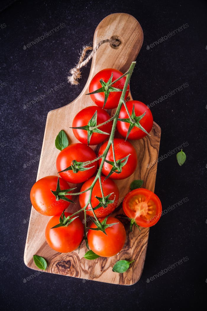 a bunch of fresh organic cherry tomatoes in olive cutting board