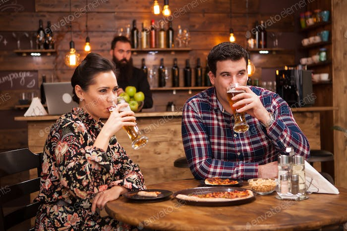 Couple relaxing at pub and eating pizza