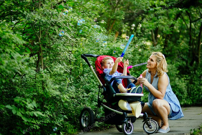 Happy pregnant woman blowing soap bubbles with child
