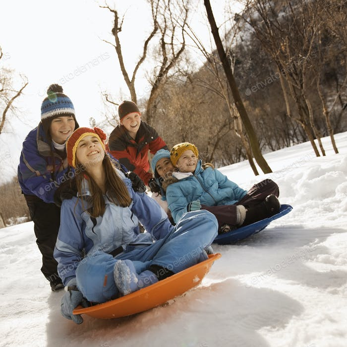 Eine Gruppe von Kindern, Jungen und Mädchen, die auf Schlitten im Schnee reiten.