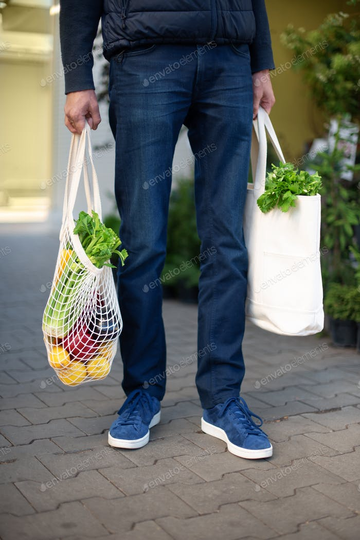 Zero waste concept with copy space. Young man holding cotton shopping bag with vegetables, products