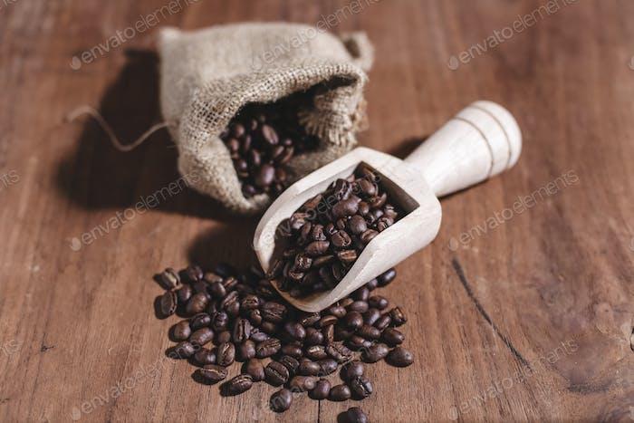 Kaffeebohnen auf Tasche und Holzschaufel