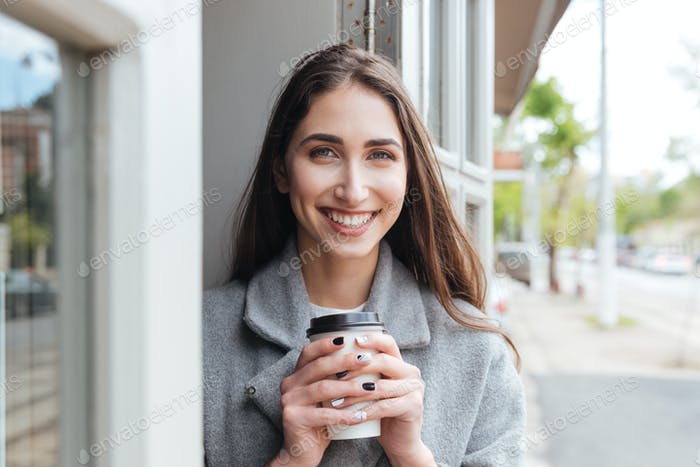 Happy cheerful smiling girl holding take away coffee