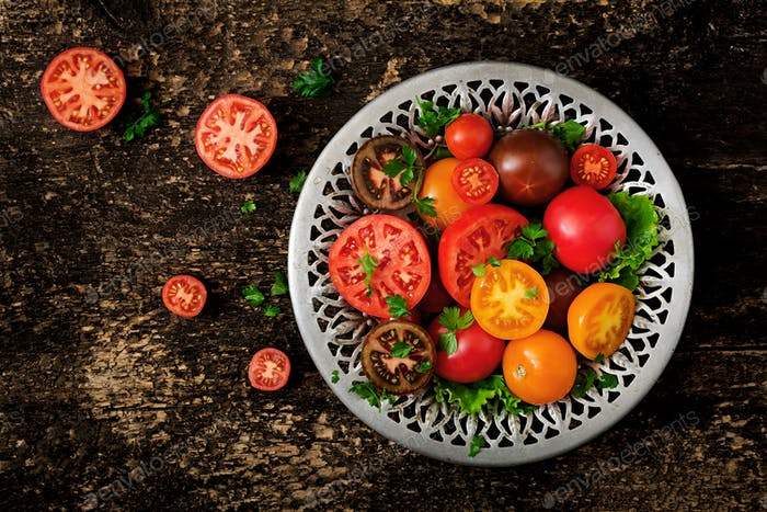 Tomatoes of different colors with green herbs in a bowl on a black background. Flat lay. Top view