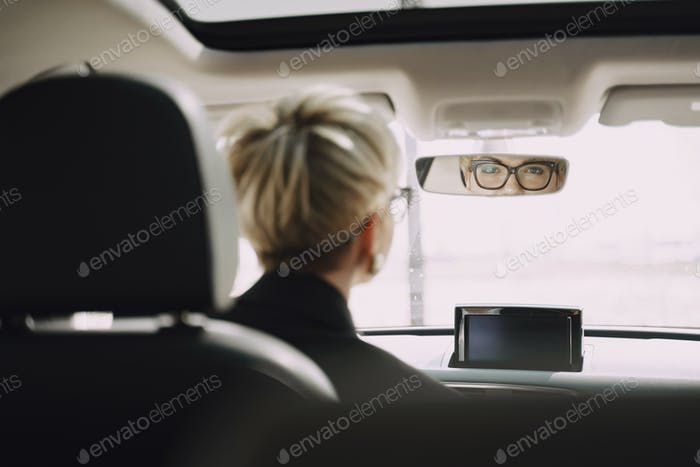 Businesswoman sitting inside a car