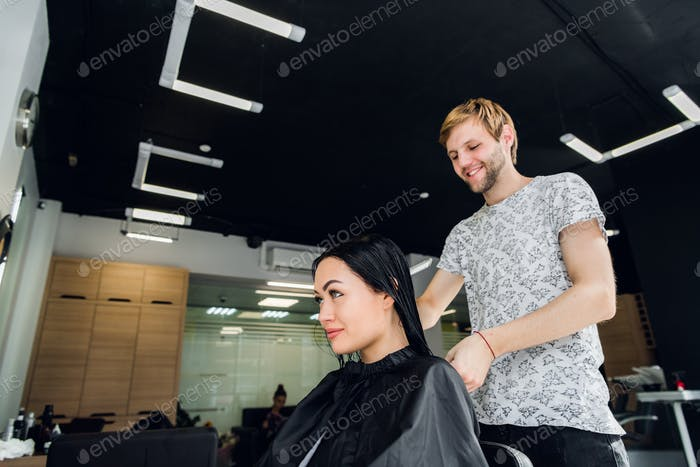 Professional hairdresser discussing female customer preferences in barbershop, choosing new hairdo