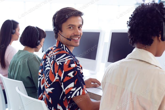 Portrait of Caucasian male customer service executive working on computer at desk in office