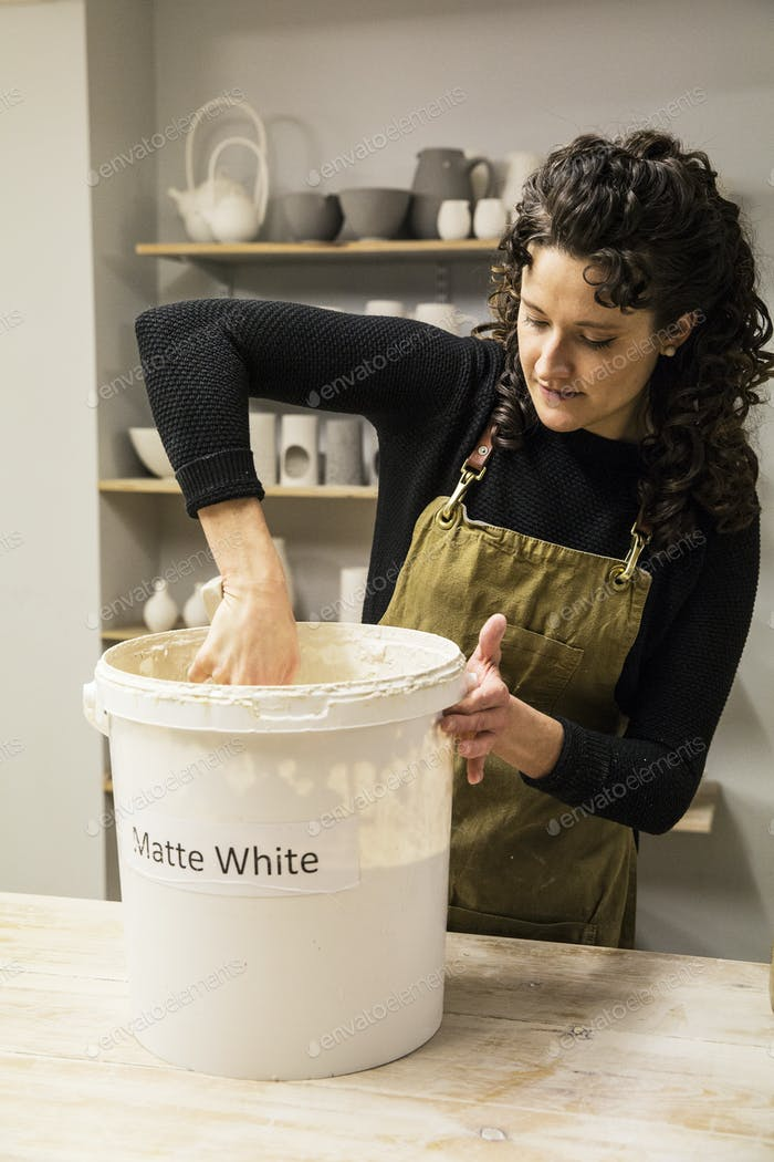 Woman with curly brown hair wearing apron standing in pottery workshop, dipping vase into pail with