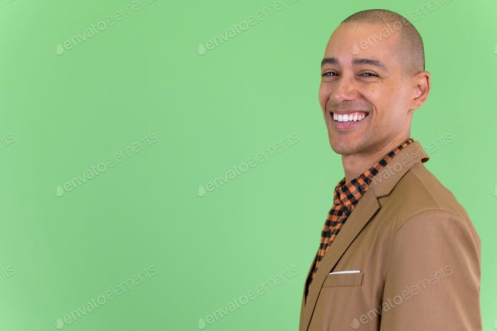 Closeup profile view of happy bald multi ethnic businessman looking at camera