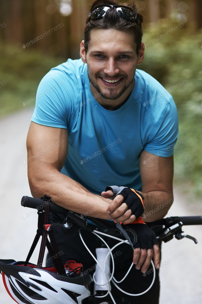 Cheerful cyclist catching his breath