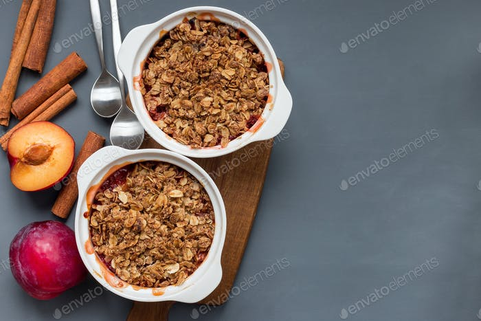 Plum crumble pie or plum crisp with oats and spices, in baking d