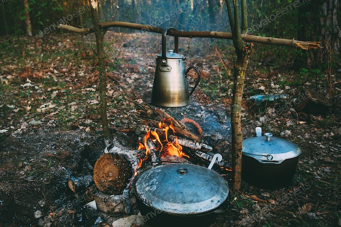 Old Retro Iron Camp Kettle And Pans Boils Water On A Fire In For