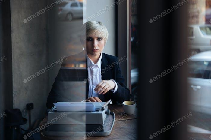 Stylish blonde girl thinking in cafe