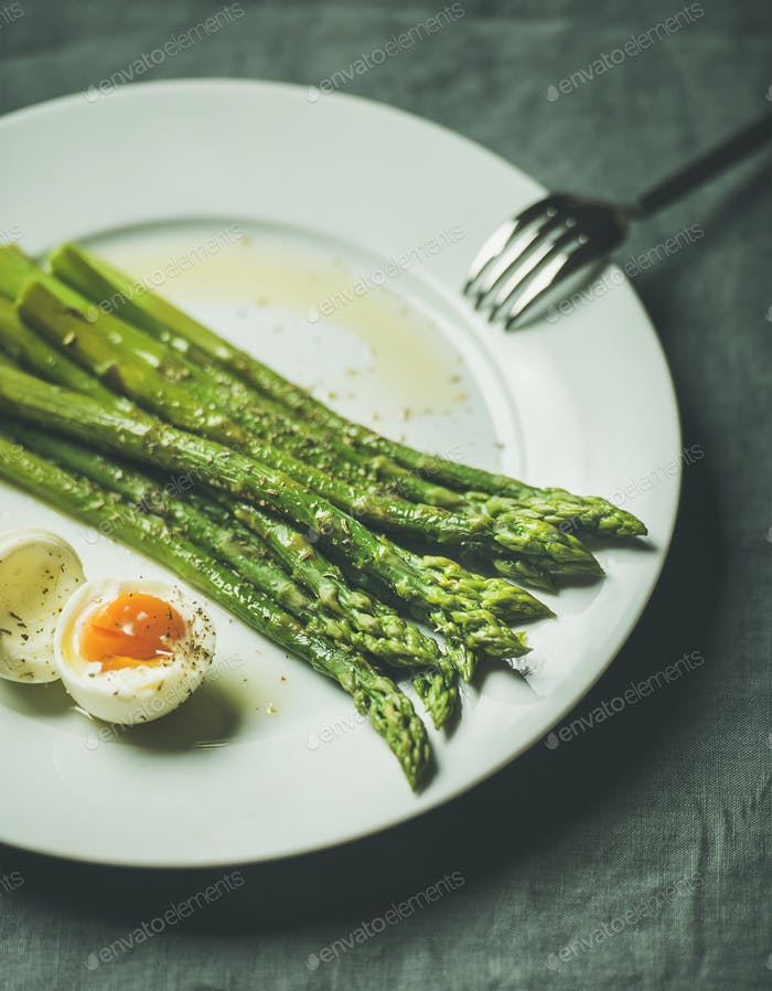 Cooked asparagus with soft-boiled egg and herbs, selective focus