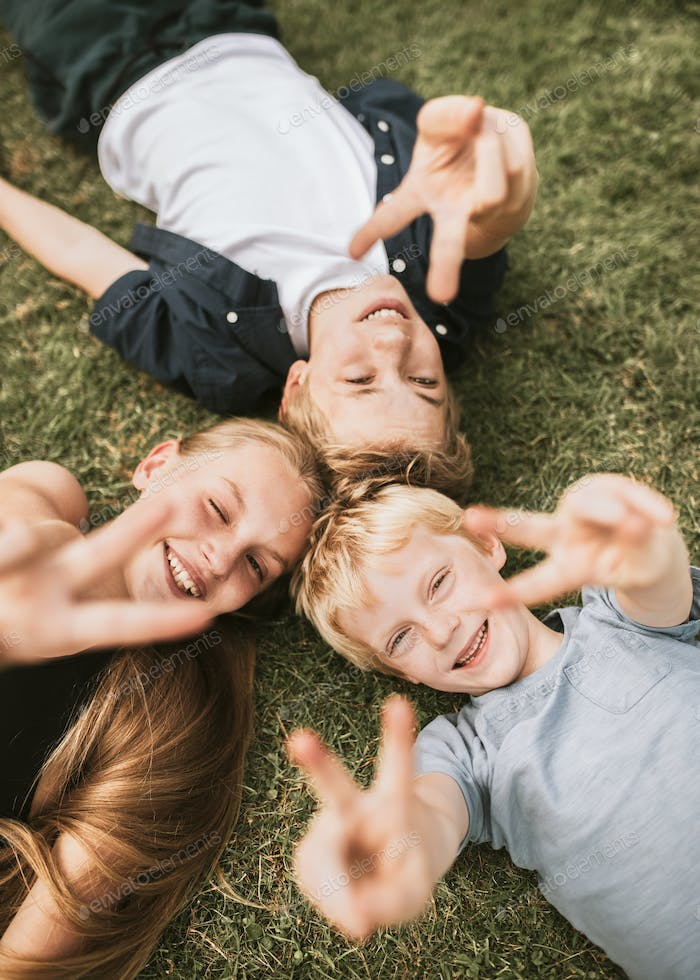 Kids lying on a grass, family photo