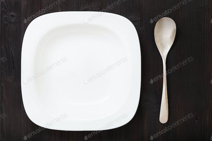 top view weiße Schüssel mit Löffel auf dunkelbraunem Tisch