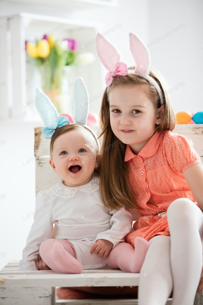Two sisters in funny bunny costumes sitting together