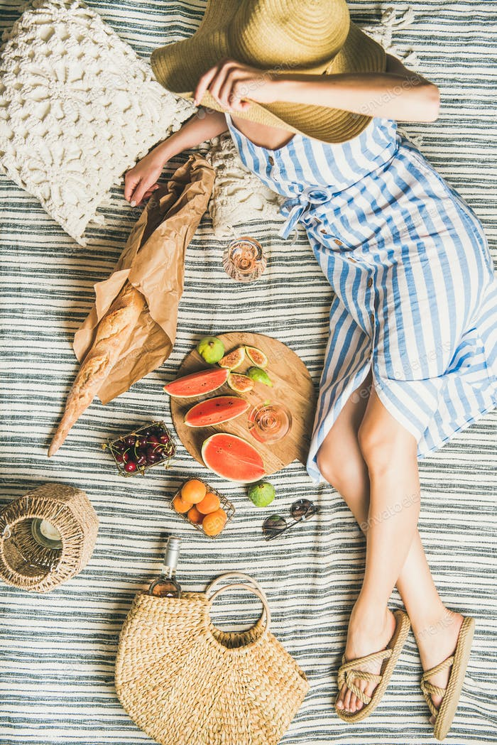 Summer picnic setting with wine in womans hands, baguette, fruits