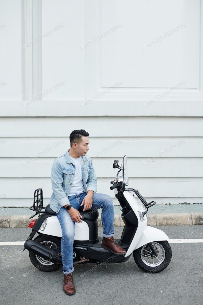 Asian Man Sitting on Moped