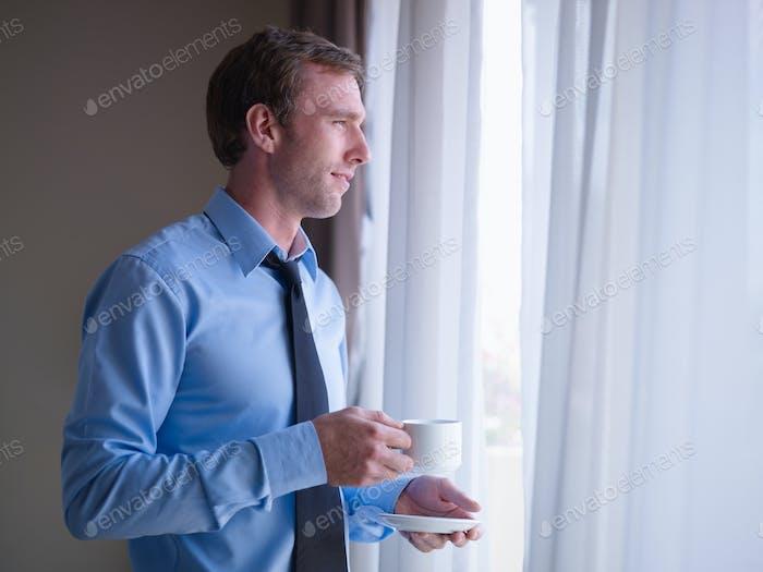 Hombre de Empresario bebiendo café y mirando fuera de ventana