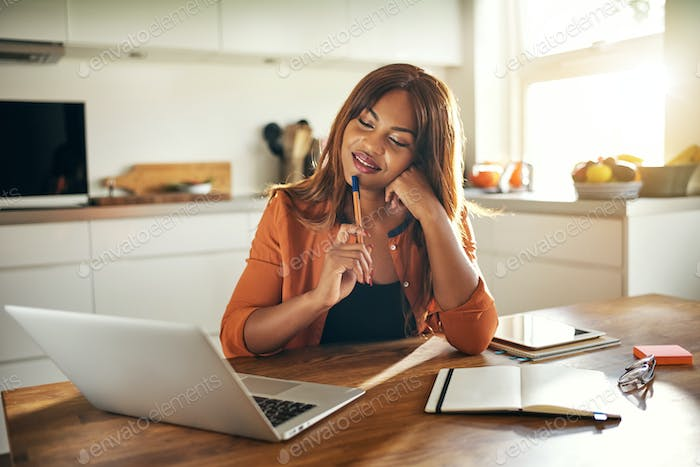 Young woman deep in thought while working online at home