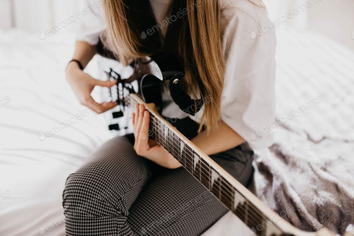 Young brunette woman playing guitar