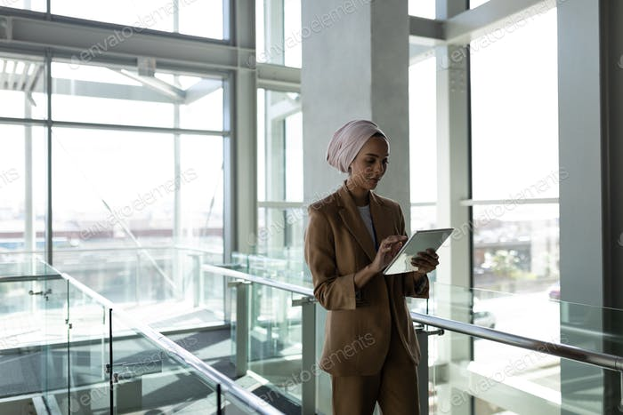 Young mixed -race businesswoman using digital tablet in office and walking on a walkway