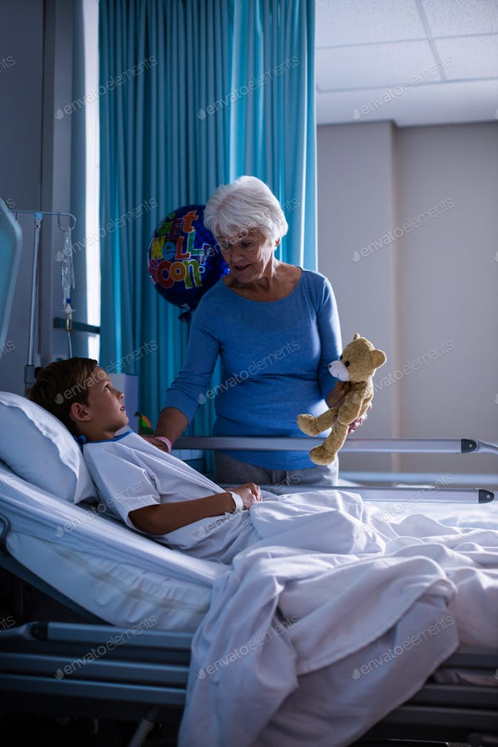Grandmother showing teddy bear to grandson