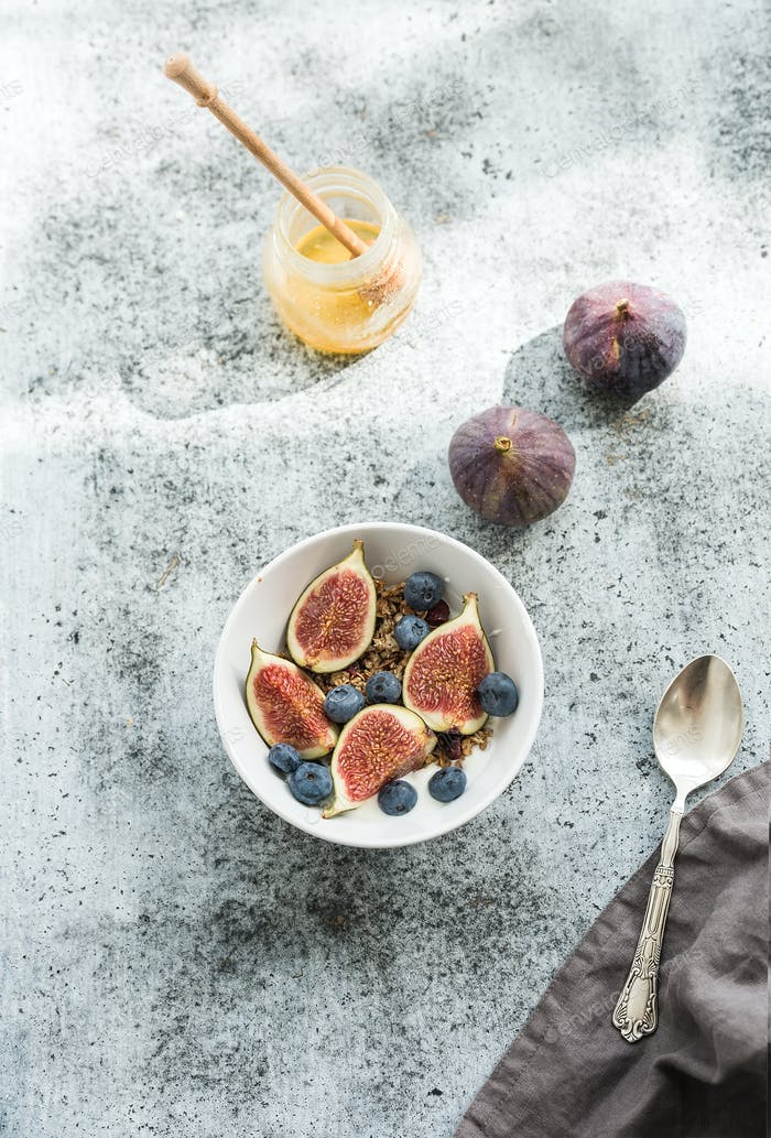 Healthy breakfast. Bowl of oat granola with yogurt, fresh blueberries and figs