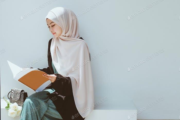Muslimische Frau beim Lesen eines Buches