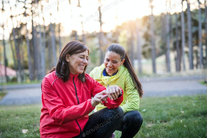 Female runners with smartwatch outdoors in park in nature, checking the time.