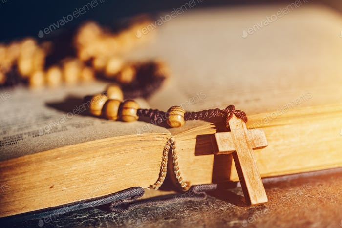 Rosary with cross laying on a Bible book.